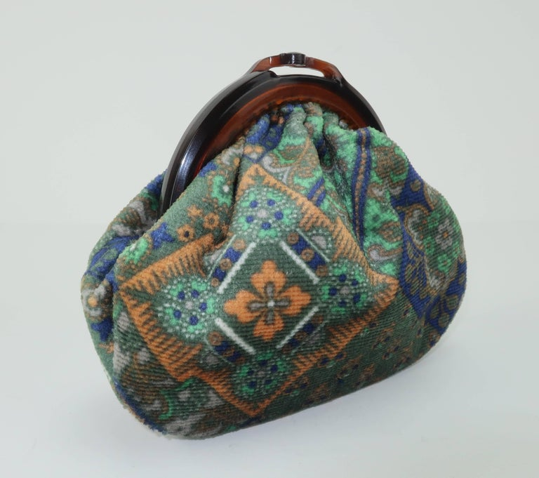 Carry your jewels in bohemian velvet style with this richly colored Italian pouch.  The kiss lock faux tortoise closure opens to reveal a buttery yellow faille fabric lined interior perfect for safe storage.  The floral fabric print is reminiscent