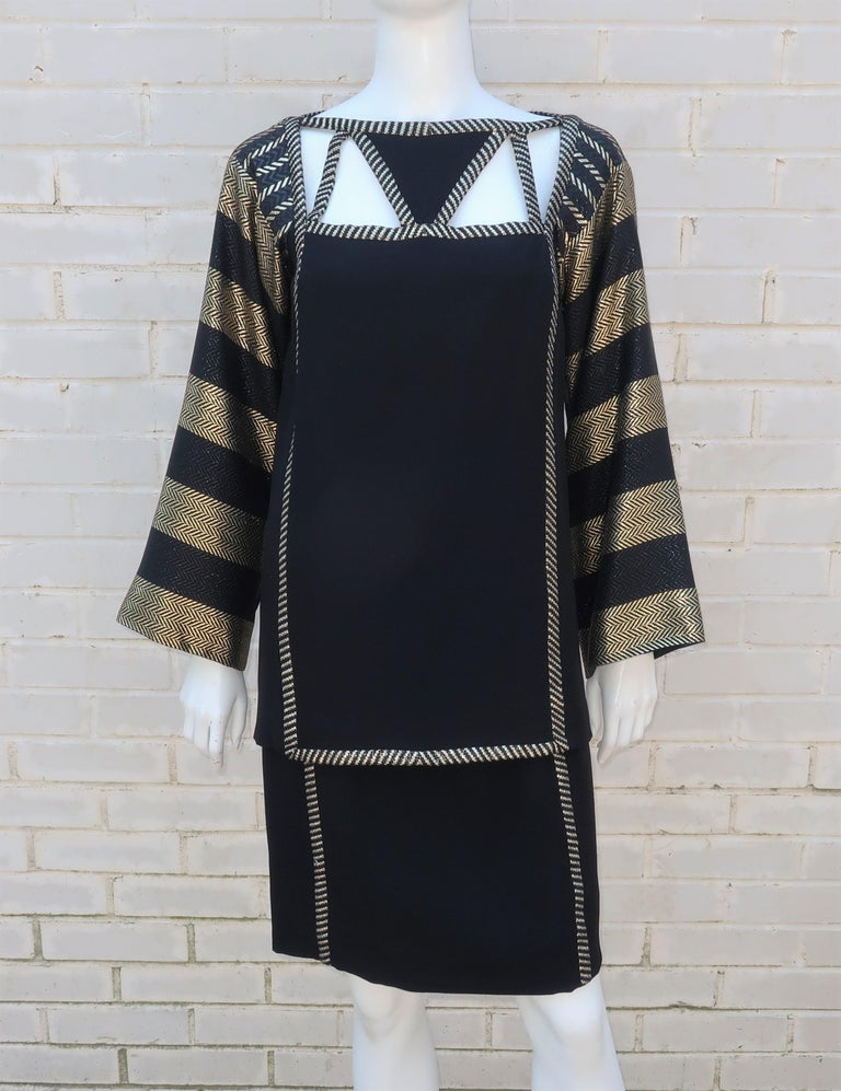 Famous for dressing fabulous divas in sequins, Bob Mackie proves with this 1970's Art Deco revival ensemble that he can dazzle without spangles and feathers.  The two piece black crepe dress consists of a tunic and skirt decorated with gold lamé