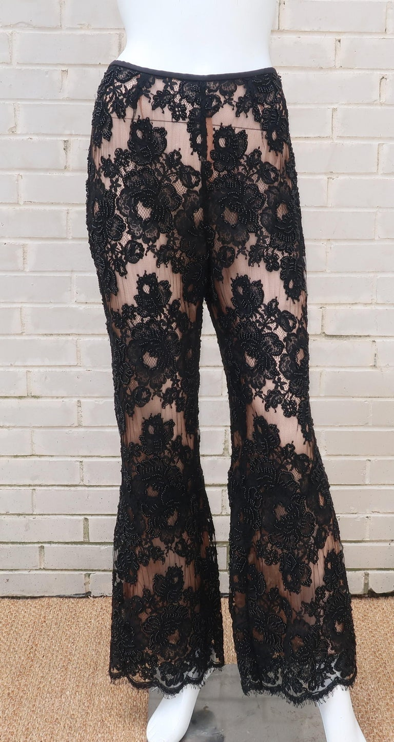 Take cocktail attire to a whole new level with these C.1990 black lace nude illusion pants.  The relaxed waist silhouette zips and hooks at the back with an overlay of intricate floral lace embellished with black beads that subtly catch the light.