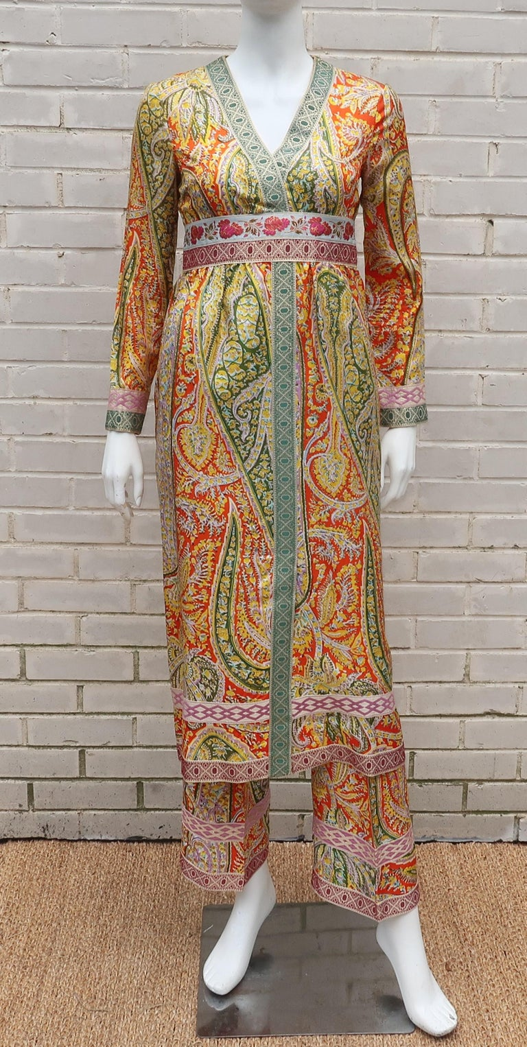 The colorful paisley print and metallic gold brocade trim on this two piece 1960's Eloise Curtis for Happenstance pant and tunic ensemble conjures up images of exotic worlds and lavish lifestyles.  The tunic dress zips and hooks at the back with a