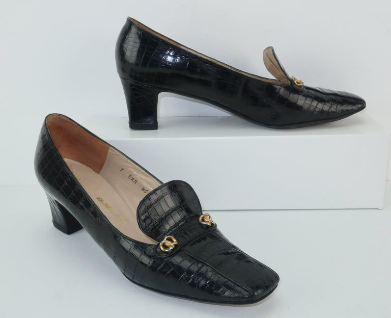 Stylish sensibility!  These Charles Jourdan C.1960 black crocodile shoes are a classic heeled loafer with stylish details including gold tone metal embellishments and a stylized vamp.  The squared toe provides a casual look perfect for skirts and