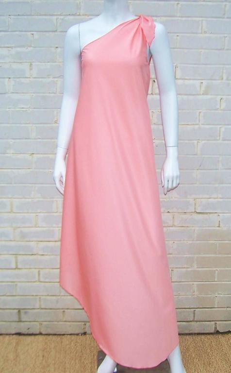 Strike a pose as a disco goddess in this Stephen Burrows one-shoulder peach jersey loungewear dress.  Mr. Burrows was lauded by the draping master, Halston, for his ability to cut a garment to perfection.  This dress is a beautiful example of that