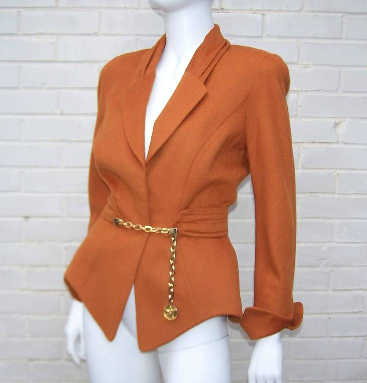 Attention to vintage style details with a unique futuristic silhouette are all hallmarks of French designer, Thierry Mugler.  This gorgeous wasp waist wool jacket is a beautiful pumpkin brown with soft pleating at the collar and a cummerbund style