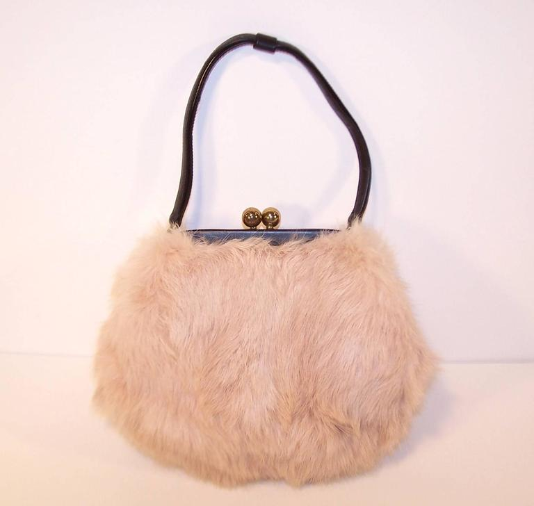 Everybody will want to touch this ballerina pink fur handbag by Morris Moskowitz ... and who could blame them.  This sweet little design has a black leather frame and handle with a kiss lock closure and silk faille lining.  The original coin purse