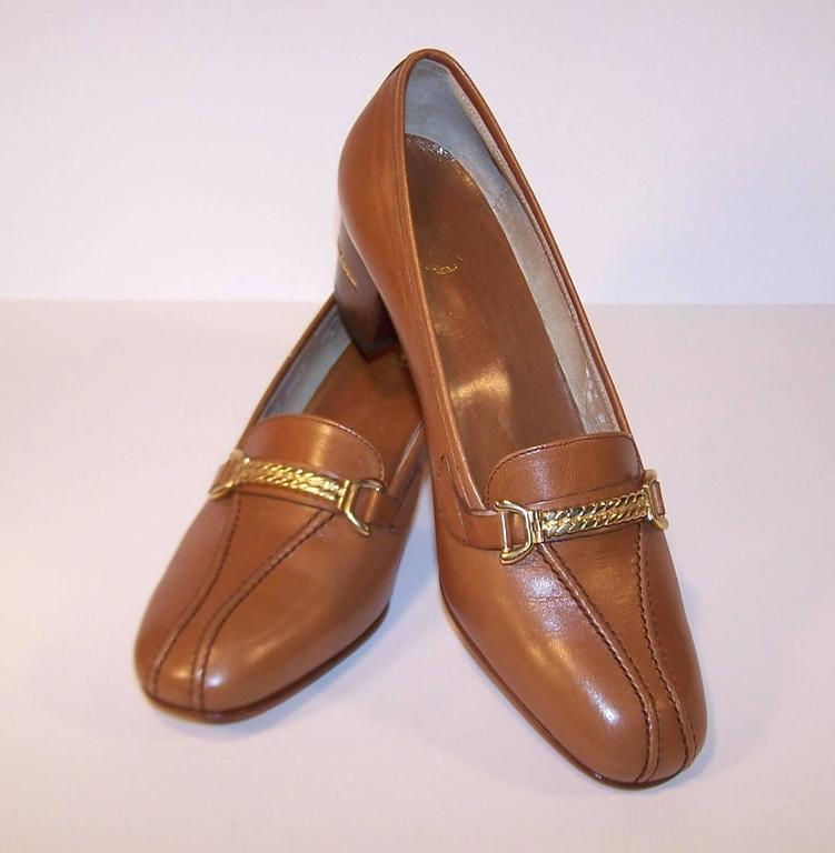 "This versatile tan leather Gucci loafer is a classic paired with trousers, skirts or jeans.  The vamp is decorated with gold braiding which is repeated on the 2"" tall wooden heels.  They appear to be unworn (maybe tried on a time or two) and"