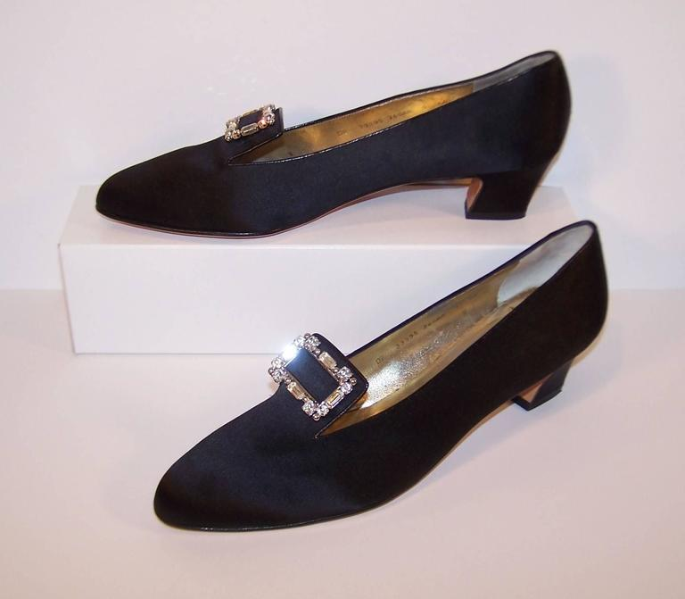 These elegant evening slippers by Ferragamo have all the comfort of modern footwear with the rich details of Edwardian style.  The black satin body is trimmed in black leather and sports square rhinestone and stud encrusted buckles.  The 2""