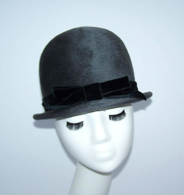 This adorable 1960's charcoal gray wool hat is reminiscent of the helmet worn by London bobbies...with a definitive feminine twist, of course!  The quality Italian made body is adorned with a black velvet bow.  Add a military inspired jacket to