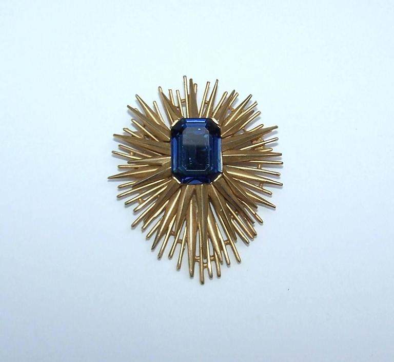 Trifari combines an edgy brutalist style with beautiful costume jewelry craftsmanship to create a starburst brooch sure to get attention.  The gold tone metal is layered with the appearance of sharp edges and serves to support a sapphire style