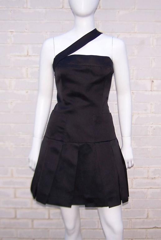 This adorable dress appears to be Chanel's take on a black tie pinafore ... with a good dose of class and style, of course.  The unique design features a wide asymmetrical strap supporting the fitted bodice which yields to a drop waist and box