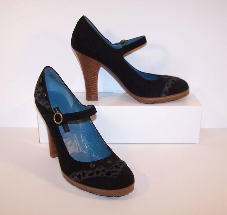 Walk on the wild side and still maintain a schoolgirl charm with these black suede Mary Jane shoes from Marc Jacobs.  The classic Mary Jane style is updated with a gray leopard printed hide trim and antique brass grommets decorating the toe and
