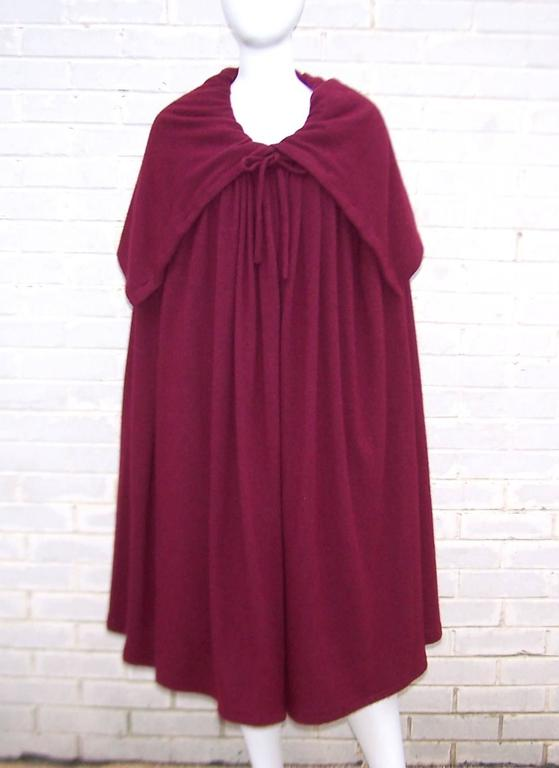 Oh the beautiful drama of a voluminous cape!  Especially when the cape is designed by Valentino Garavani in an aubergine red angora wool blend that drapes with all the comfort of a cozy wrap.  The cape ties at the neckline and buttons on the
