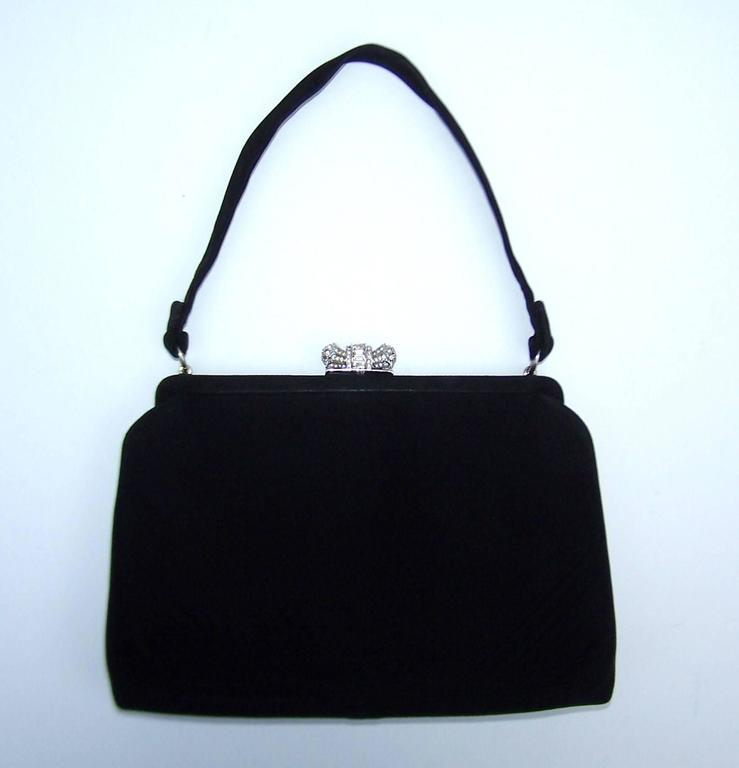 This classic 1950's top handled handbag by Coblentz is a perfect vintage accessory for a modern evening ensemble.  The black suede body is roomy enough for the essentials and the jewelry style rhinestone embellished closure adds just the right
