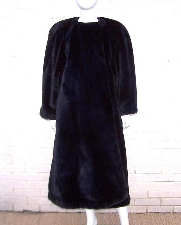 What a great bear hug of a coat!  From the late great Sonia Rykiel, this voluminous jet black faux fur coat has all the inspiration of a 1940's silhouette including broad shoulders and high drama. The coat buttons at the neck with a large faux fur