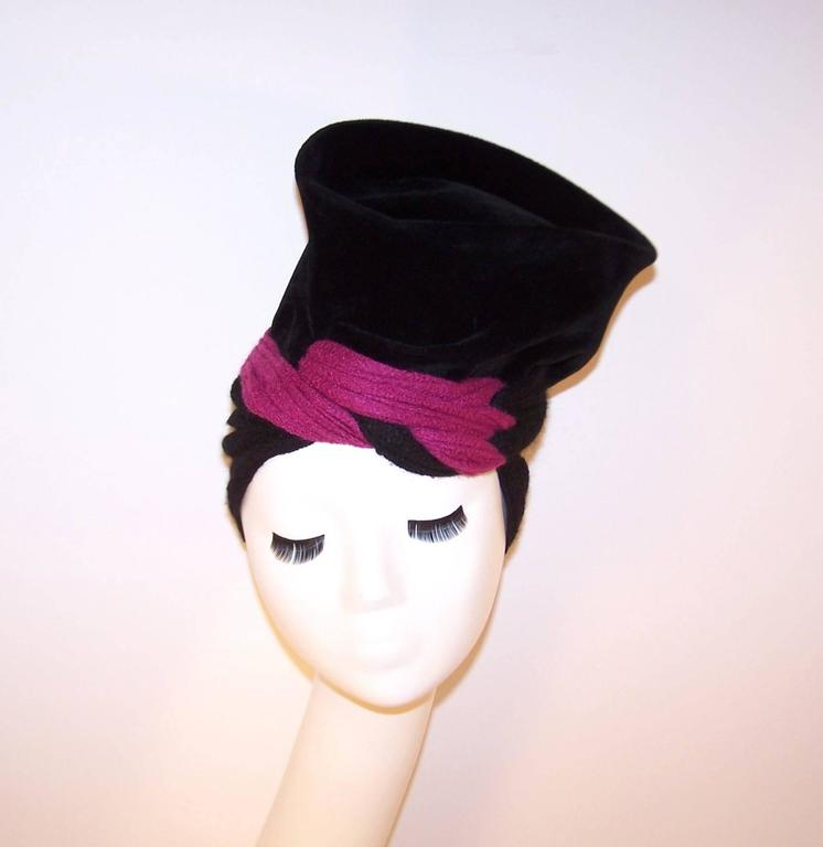 You are going to have so much fun with this hat!  The soft velvet body stands tall with a sculptural shape and the stretchy wool knit snood anchors everything in place.  The fuchsia pink color pop is an added bonus and makes this avant-garde hat a