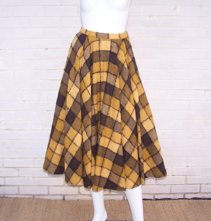This voluminous checkered golden yellow, brown and black wool skirt by Herbert Labandter  is the perfect 1950's circle silhouette.  The skirt hooks and zips on one side with a generous side pocket on the other side.  The checkerboard print is