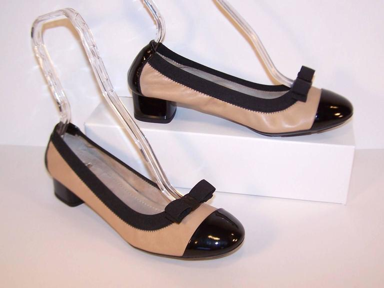 This contemporary version of the classic Ferragamo ballet flat has a couple of updates that are sure to please.  Start with the elastic collar and add soft nude leather with black patent highlights at the toe and low heel.  Add a skid proof rubber