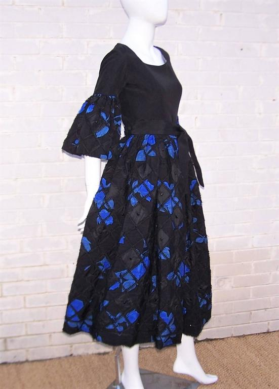 Fabulous!  Adolfo's designs from the 1970's are the epitome of ladylike charm and this two piece dress ensemble is here to prove it.  The pieces have a folkloric peasant dress style assembled from heavy black silk moire and coordinating electric