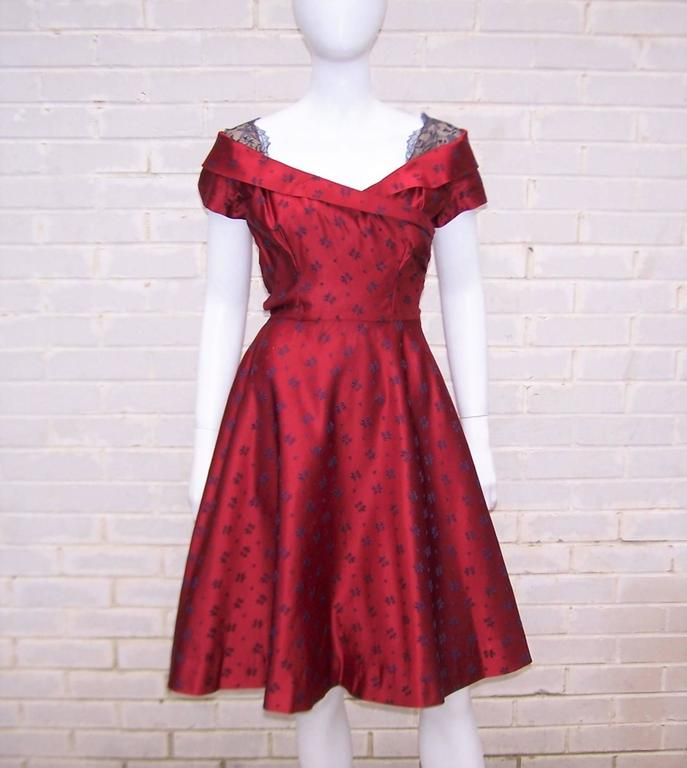 This early Adele Simpson design is the epitome of a fun party dress.  The cherry red satin fabric is accented with navy blue flowers and provides the right amount of stiff structure to create both a cinched and flared silhouette.  The dress zips and