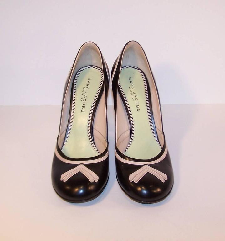 These two tone leather pumps by Marc Jacobs have all the sass and style of a 1940's era pin up girl.  The black leather background is embellished by pink fleshtone trim resembling a trompe l'oeil tie at the vamp. (They could also pass as midnight