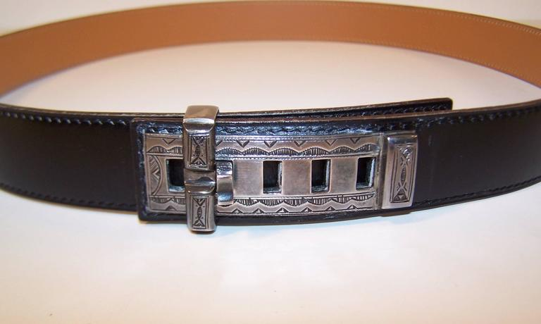 This unique Hermes 'Touareg' black leather belt features a hand crafted sterling silver buckle with a North African tribal motif.  The closure is a 'collier de chien' style with five adjustments and a sliding bar to keep everything in place.  The