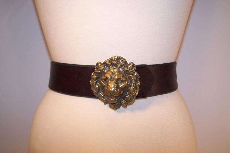 The stately antiqued brass lion buckle is the perfect foil for this thick brown saddle leather belt.  The buckle is marked England on the back and has a hook which securely fits into four adjustable options on the belt.  Both a combination of