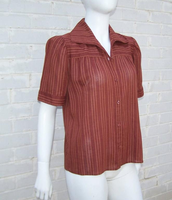 An airy and effortless 1970's linen top by Yves Saint Laurent which is perfect for the warm days of Summer and the mild days of Fall.  The reddish brown striped fabric is expertly cut to provide horizontal stripes across the shoulder with vertical