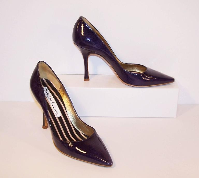 These stiletto shoes have all the classicism of a 1950's silhouette with a dash of Christian Lacroix's modern magic in the form of a unique mottled surface creating a subtle purple undertone to the blue laminated leather.  Add a striped satin foot