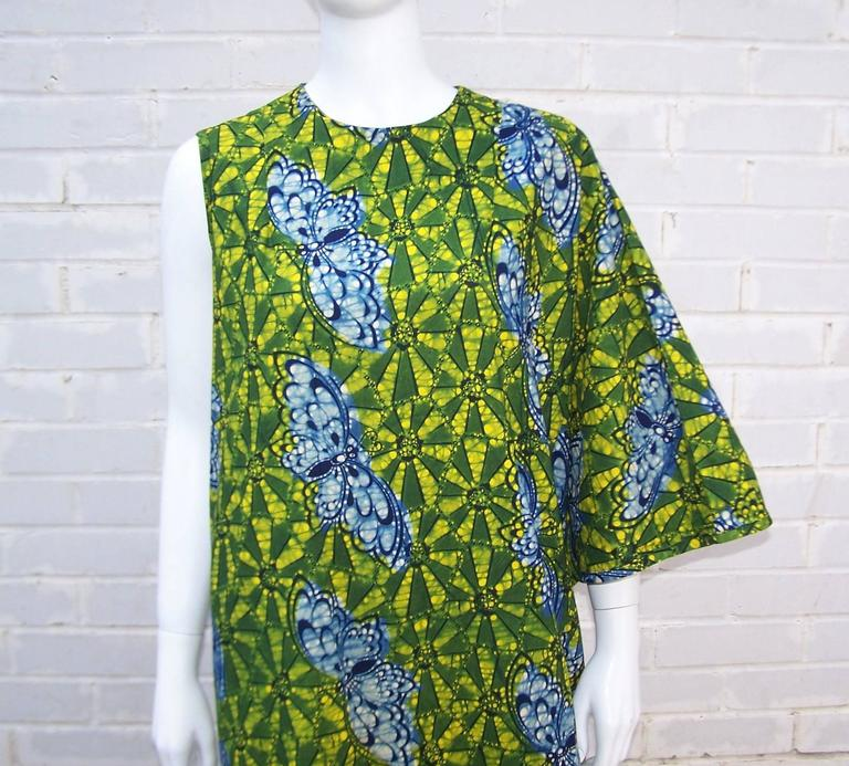 This asymmetrical caftan is a great combination of glamour and 1960's psychedelia all wrapped up in a colorful batik printed cotton fabric.  The lush greens, yellows and blue colors are reminiscent of a tropical rain forest and the design also
