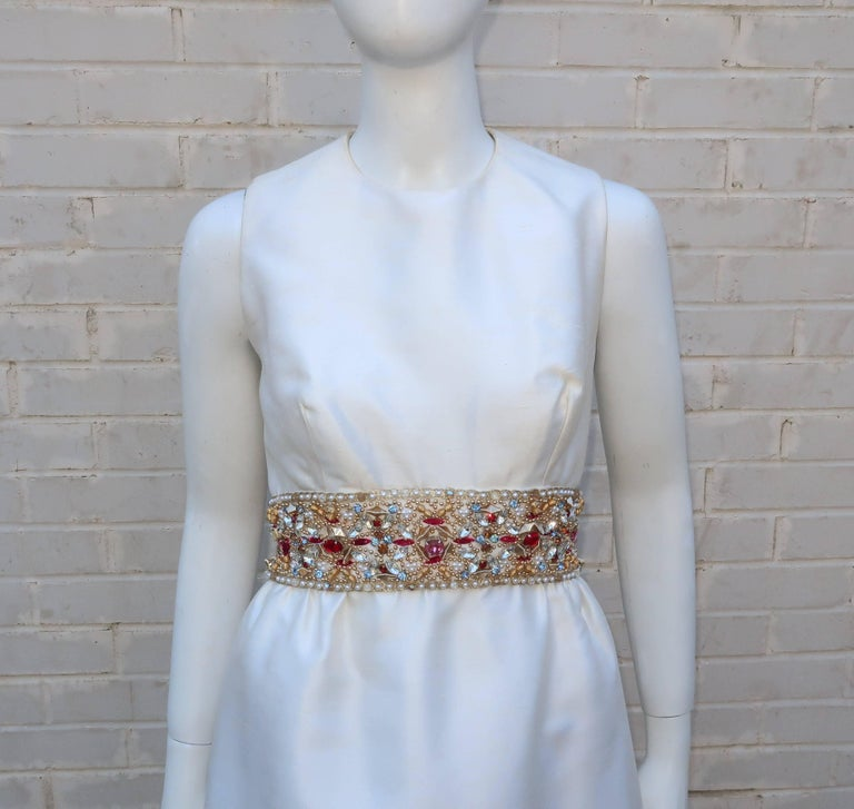 Prepare to be bedazzled!  This 1960's Kent Originals evening dress in a crisp white dupioni fabric is a classic 1960's empire waist silhouette with a couple of eye catching features.  First and foremost is the dazzling embellished empire waist with