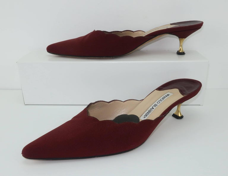 Meet the current mule trend with these fabulous Manolo Blahnik dark burgundy faille fabric shoes.  The scalloped edged vamp with a perfect pointed toe are feminine details that are further enhanced by the gold metal tipped kitten heels.  The rich