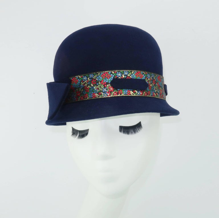 Give the classic bowler hat a ladylike twist and voila!  This adorable navy blue wool felt hat appears and provides a stylish topper that provides warmth and charm to a wintry ensemble.  The shallow brim is charmingly decorated with a floral brocade