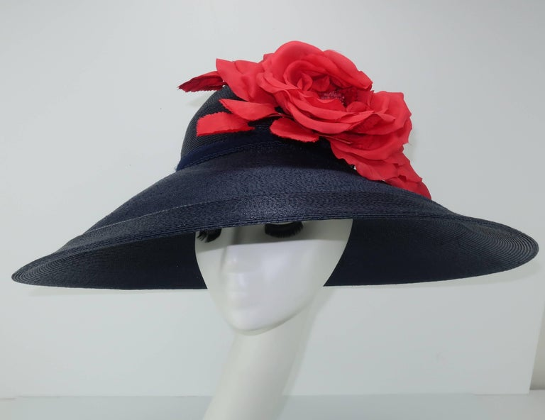 Garden party anyone?  Patricia Underwood has mastered the millinery skill of creating fashionable toppers that compliment silhouettes without too much adornment.  This wide brim blue straw hat is a bit of departure with a beautiful oversized red