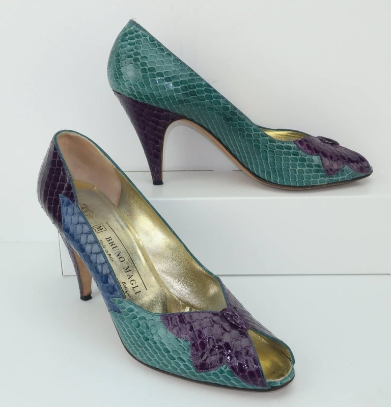 Bruno Magli has been producing quality Italian leather goods since 1936.  These ultra feminine peep toe pumps are a beautiful combination of jade green, blue and plum snakeskins with an abstract design at the vamp reminiscent of a butterfly.  The