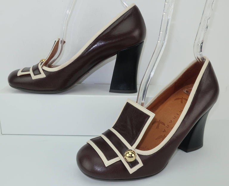 These contemporary shoes by Chie Mihara are a great homage to the fabulous mod footwear styles of the 1960's.  The two tone leather body combines a dark chocolate brown with an off-white trim in a graphic pattern embellished with a gold ball detail