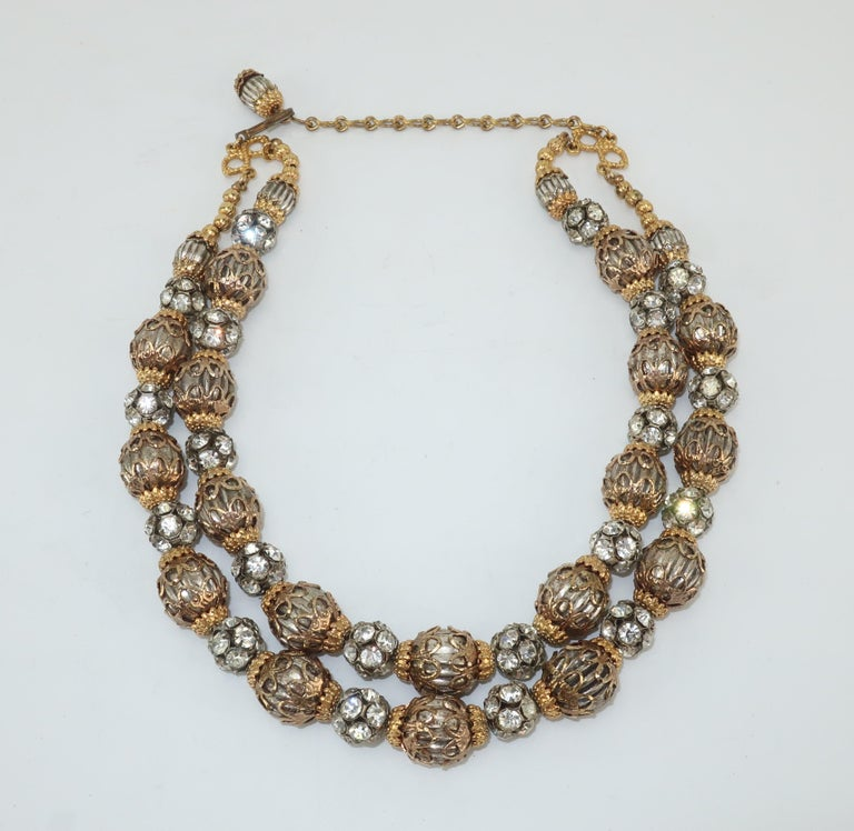 A 1950's dazzler!  This two stranded necklace consists of silver tone fluted beads with gold tone filigree caps interspersed with rhinestone encrusted beads.  It is outfitted with adjustable hook and chain enabling wear as a choker or short necklace