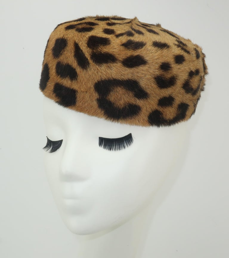 Add an exotic flavor to your wardrobe with this fashionable leopard printed fur pillbox hat.  The minimalist shape can be worn forward, back or cocked to one side.  Lined with grosgrain black fabric and accompanied by a vintage hat box from Muse's,