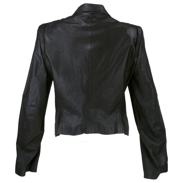 Trench style double breasted jacket in black leather by Ann Demeulemeester. Fully lined with slash pockets and distressed look texture. Foldover collar detail.