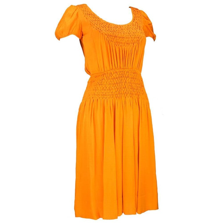 Incredible 1970s dress by Christian Dior-New York.  Orange silk peasant style with hand smocking detail at bodice and waist, reminiscent of Eastern European dresses from the 1920s.  Fully lined with poufed cap sleeves.