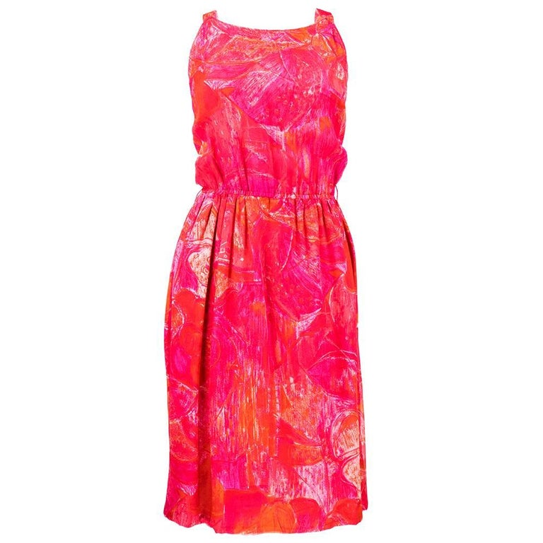 Vividly printed tropical floral silk chiffon dress from Pierre Cardin comes with a matching cape that attaches invisibly to the dress straps with a hook and eye. Print is a hot pink and orange painterly tiki inspired floral. Dress has a scoop neck