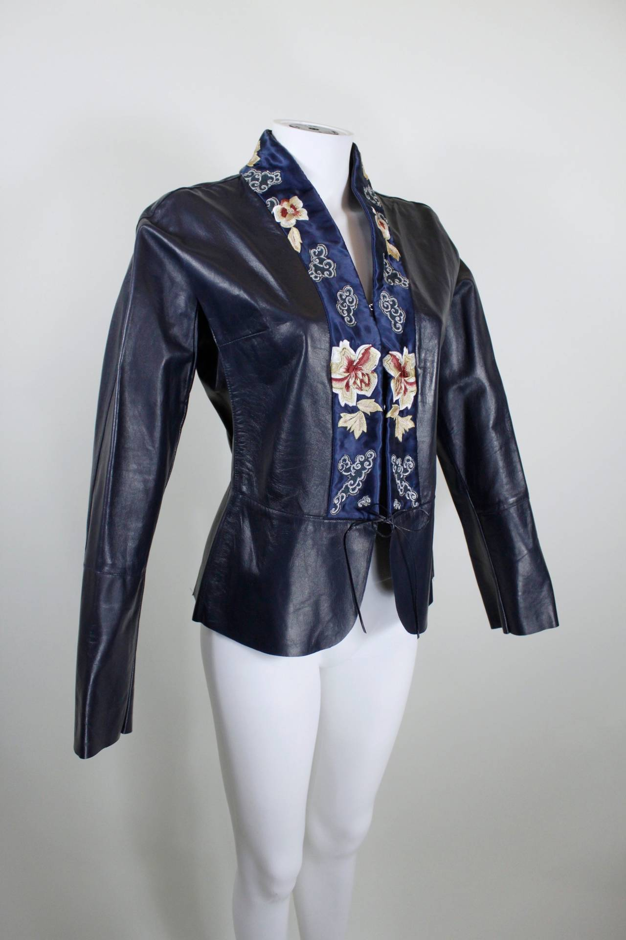 A gorgeous jacket from Blumarine done in supple, lightweight navy leather. A kimono-style silk collar is embroidered with Japanese-inspired floral motifs. The jacket closes with two hook-and-eyes and a thin leather cord at the waist. A slight peplum