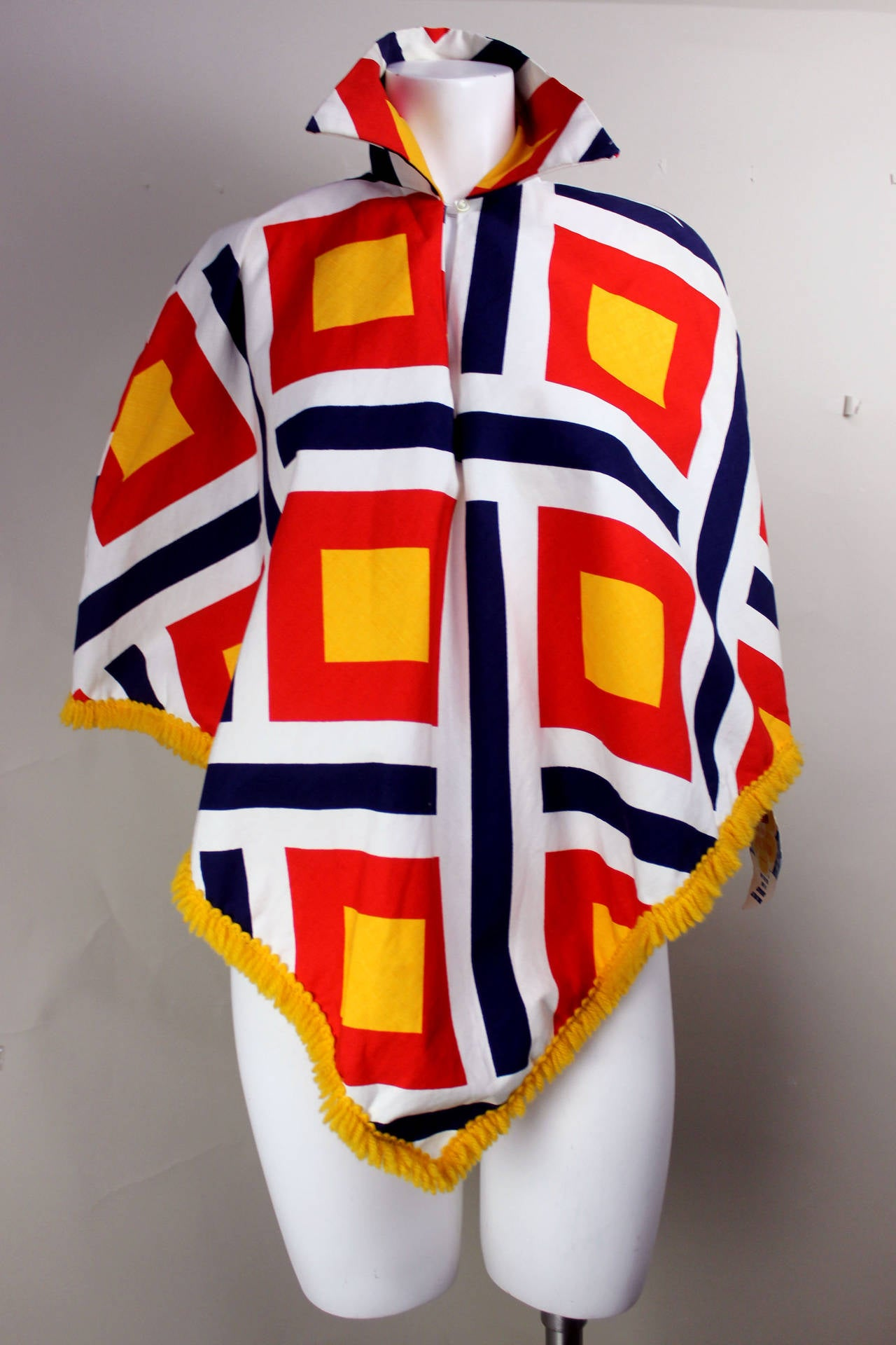 This never worn late 60's early 70's beach poncho is an exceptional find. The bold geometric print is in marigold, red, and navy, with the addition of a marigold fringed yarn trim. This is an iconic piece of vintage beach wear with all of the