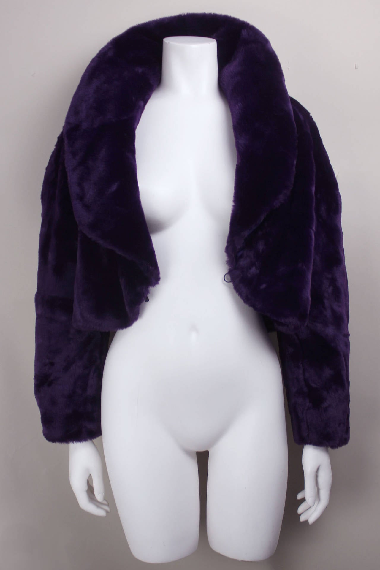 This jacket is of a very luxurious deep purple pile and has a generous shawl collar. It is cropped at the waist in the style of a 1970s chubby jacket.