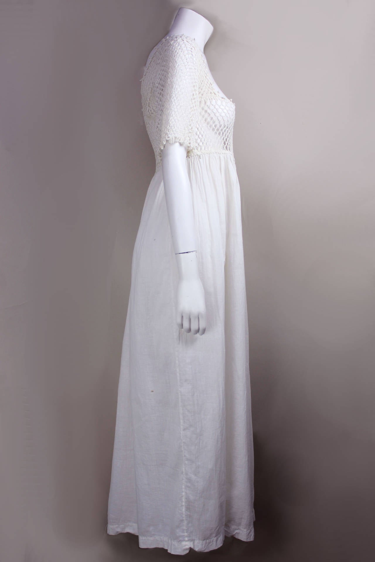 Unique and delicate, this piece dates to the Edwardian period (1901-1910). The skirt is made of a light crisp cotton and the scoop neck bodice of an intricate crochet. The airy quality of the gown can be attributed to the shift towards softer and