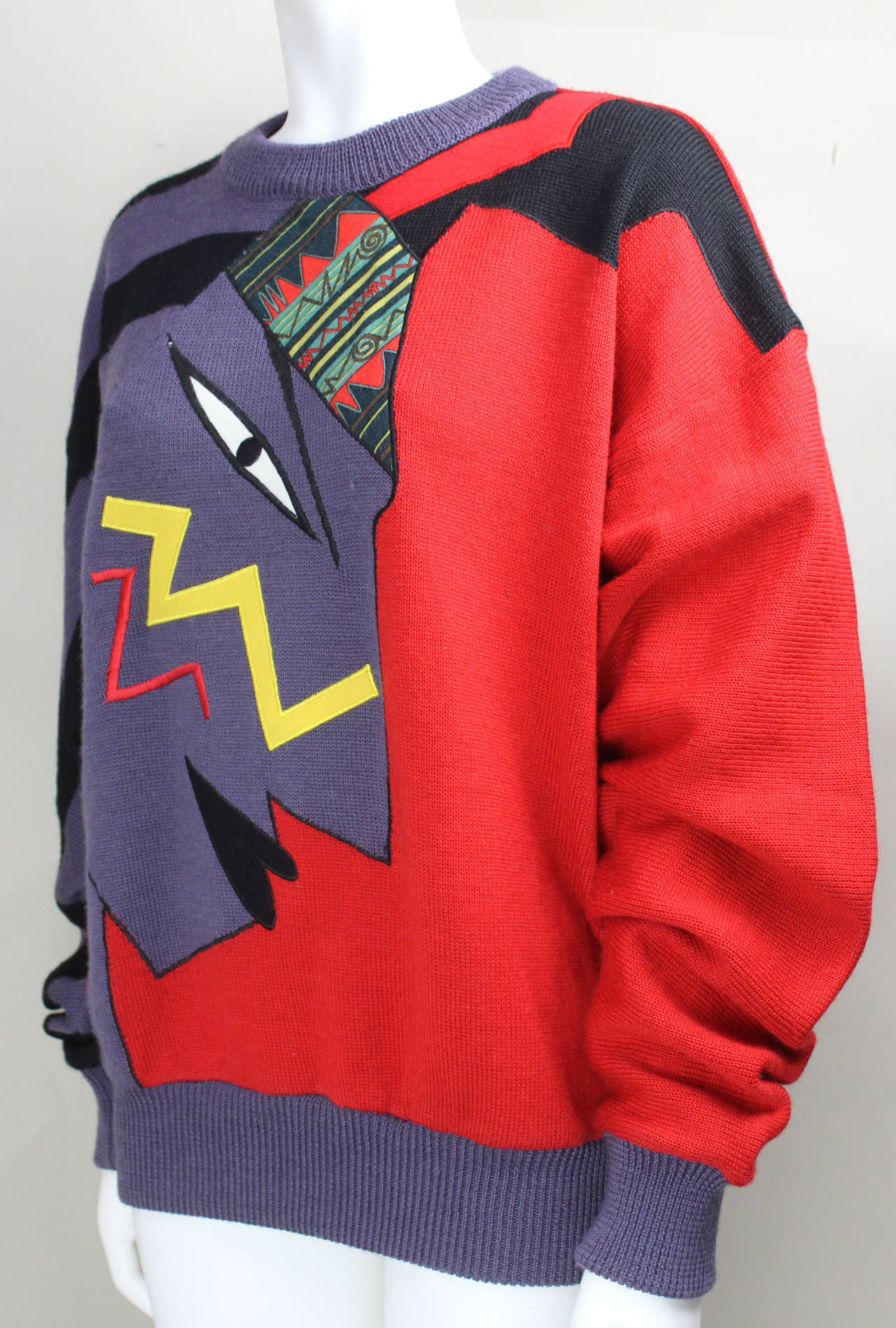 Red and purple knit with a graphic face design. Kansai Yamamoto's innovative, vibrant, wearable art is another example of Yamamoto's contribution to Japanese Contemporary fashion.