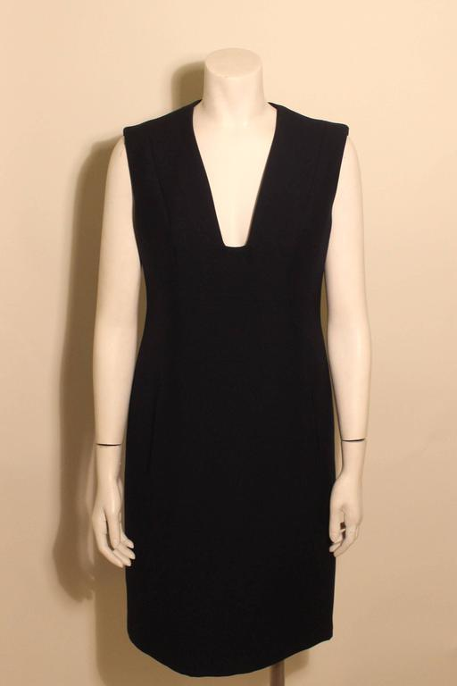This navy Trigere dress is a classic timeless design. It has a deep v neckline and two front pockets. This chic dress is made of a fine wool and is completely lined.