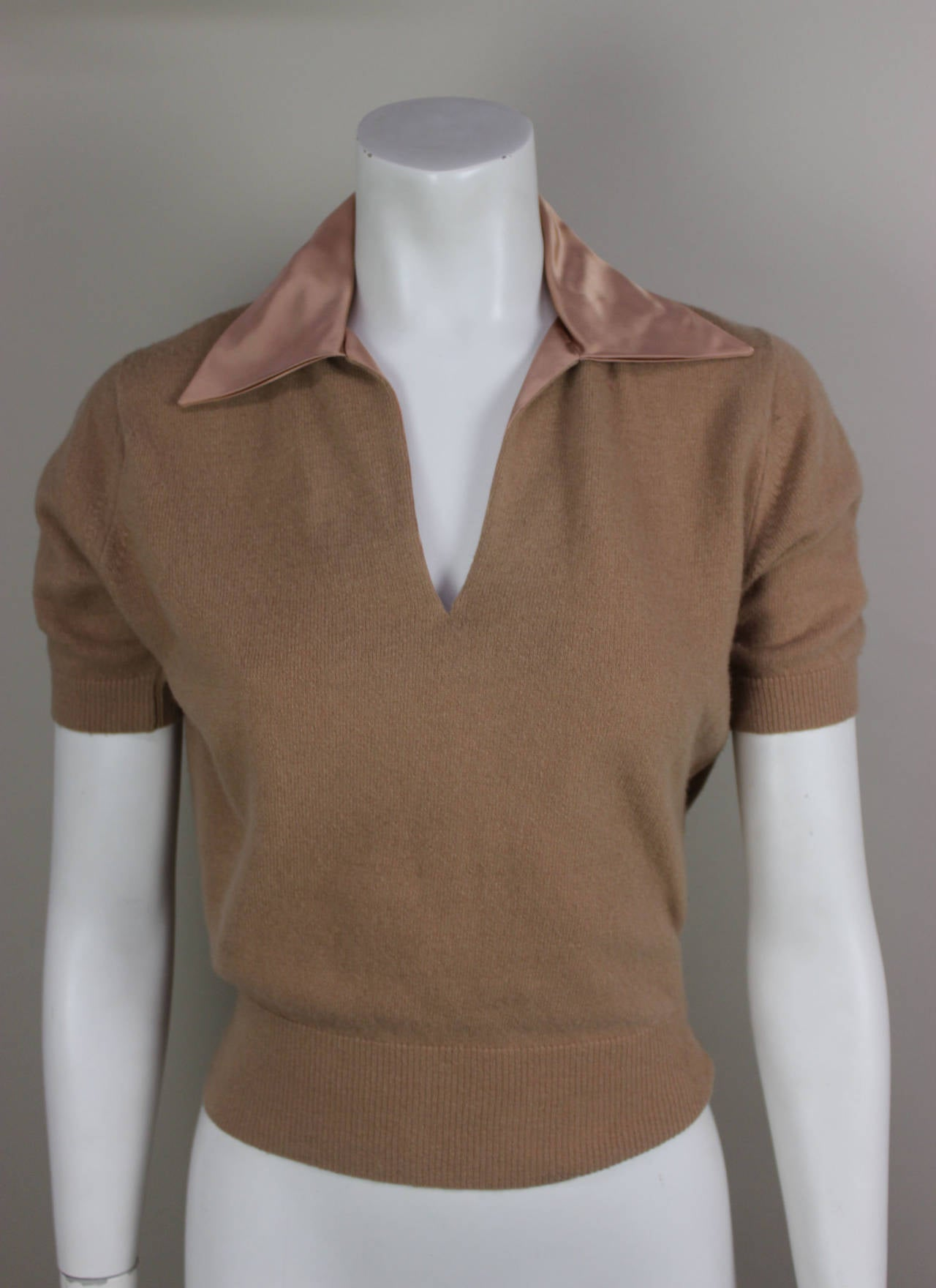 """SALE! Originally $275 In the 1950's, short sleeve cashmere sweaters were all the rage! This piece is in a lovely carmel color with a matching satin collar. The label reads """"A Cadillac Original"""" with the cars trademark at the top. Cadillac was"""
