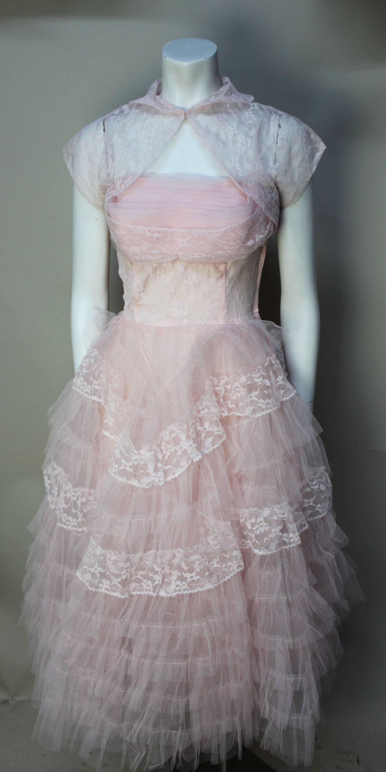 This soft pink tulle confection is a 1950's gem of a dress. An intricate bodice of pleats and lace tops a three layer bottom of ruffled tulle with a taffeta underslip. The matching lace bolero is classic 50's style. This dress is quintessential