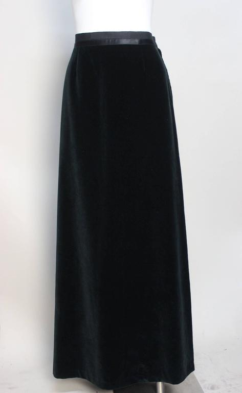 Previous to 1997, Margiela's early clothing was marked by a blank white label with his trademark four white stitches. This long fitted skirt is in a dark forest green lush cotton velvet. There is a band of grosgrain topped with satin ribbon at the