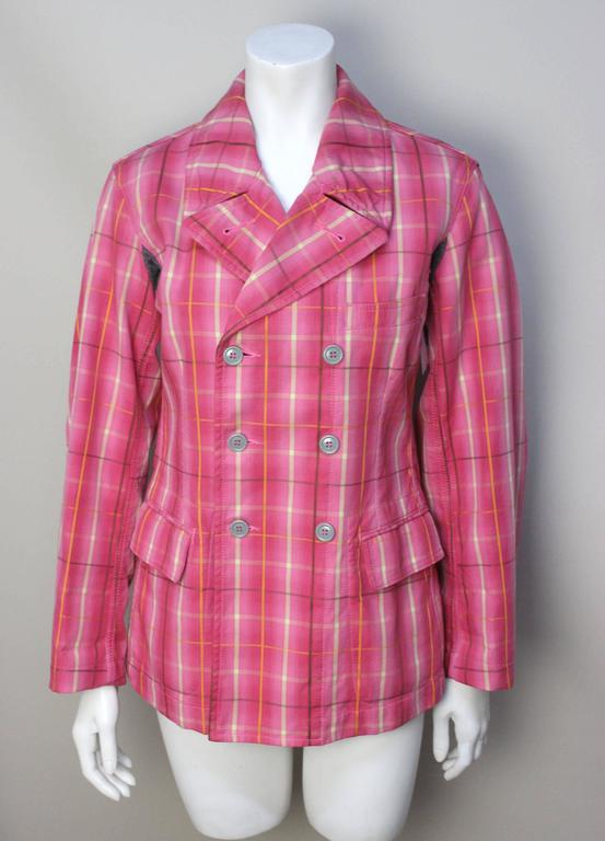 This vibrant pink plaid jacket has a quirky detail of grey wool armpit inserts that tags it as a Comme Des Garcons design. The body is fitted and double breasted. The bright cotton plaid fabric is lined in an earth tone corduroy, another eccentric