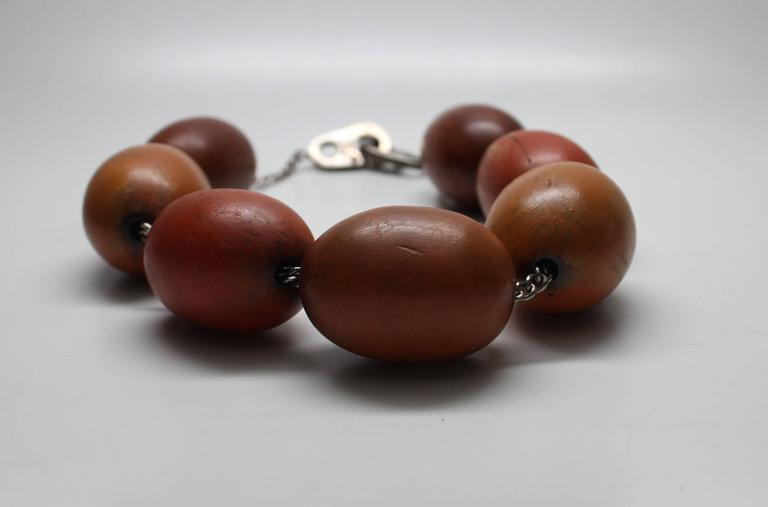 This statement necklace has 7 large polished egg shaped wood beads on a sterling chain with a sculptural sterling clasp.